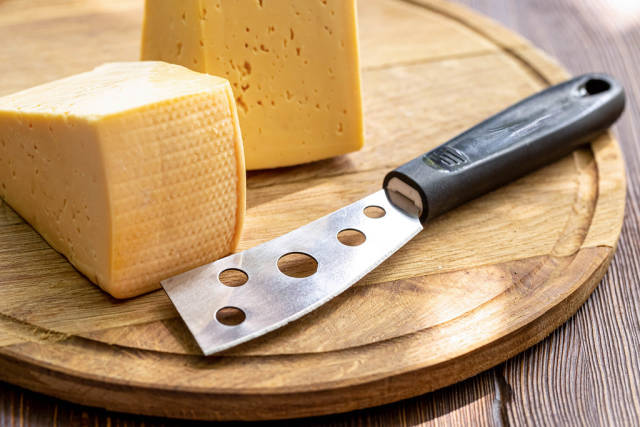 Two pieces of cheese and a cheese knife on a wooden kitchen board
