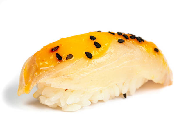 Nigiri with sea bass fillet and mango sauce on a white background