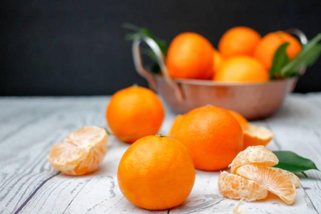 Klementinen mit Blättern auf weißem Holztisch