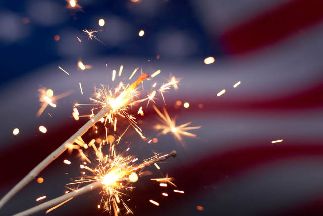 Burning sparklers against USA flag. Celebrating US national holiday with sparklers