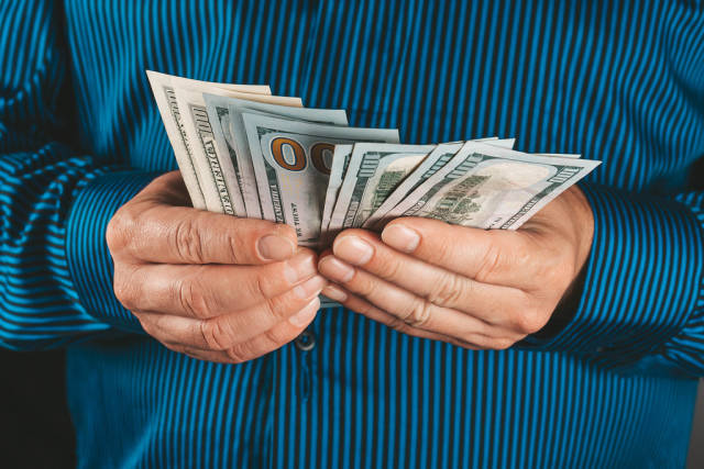 Close-up, a man with a blue shirt holds dollars in his hands