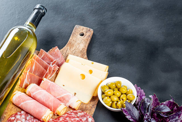 Bottle of white wine, fresh Basil, cold cuts, cheese with green pickled olives on black background