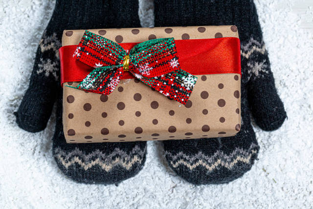 Childrens hands in mittens are holding a gift on a snow background. View from above