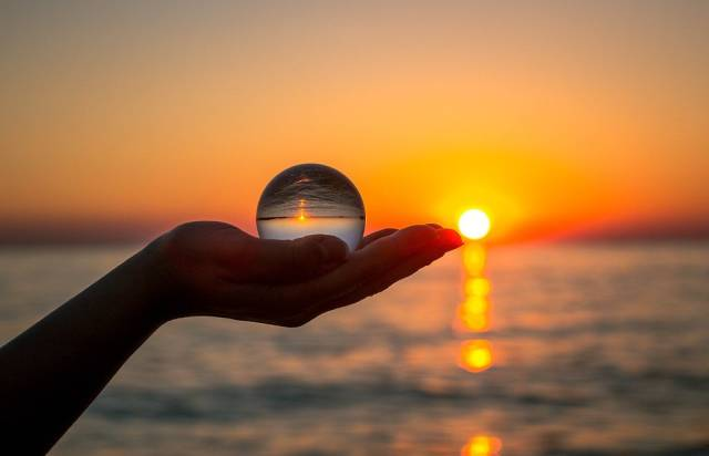 Mindfulness - Glass ball in girls hand during sunset at the beach