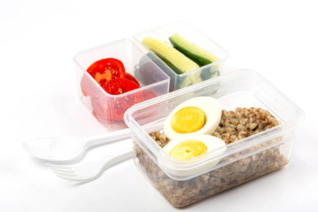 Buckwheat porridge with boiled eggs, pieces of fresh cucumbers and tomatoes in plastic containers