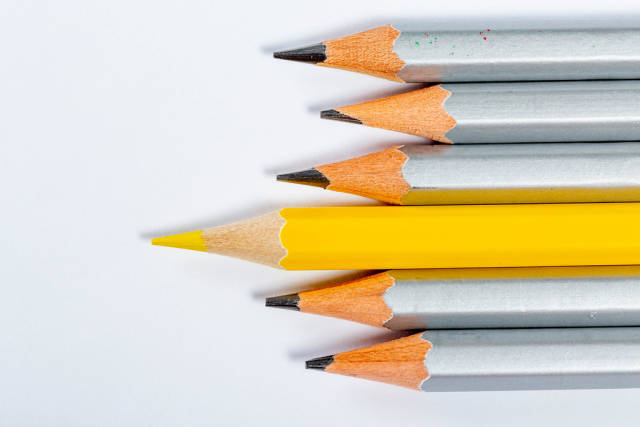 Yellow pencil standing out from crowd of plenty identical grey fellows on white background