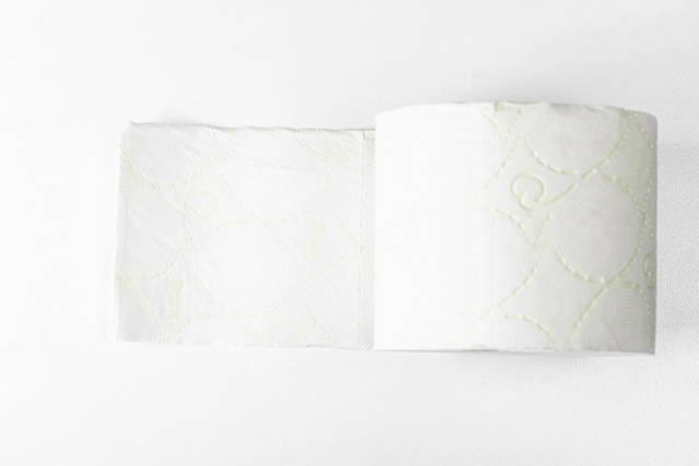 Rolle weiches, weißes Toilettenpapier auf weißem Hintergrund. Aufnahme von oben