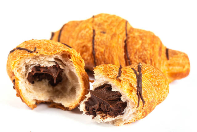 Fresh croissant with chocolate filling on white background