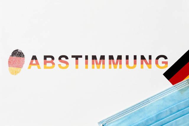 Abstimmung für den deutschen Bundestag mit OP-Maske während der Covid-19 Pandemie