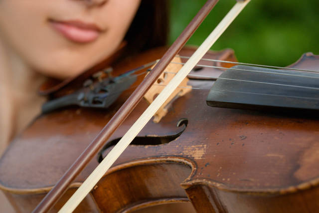 Girl playing on the old violin outdoor, close up