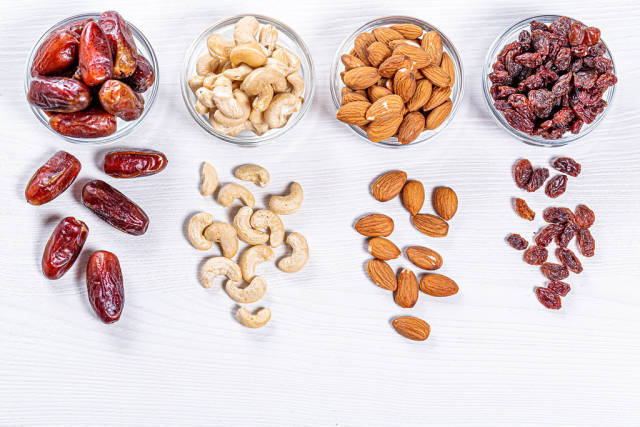 Dried dates, raisins, cashew nuts and almonds on white wooden background