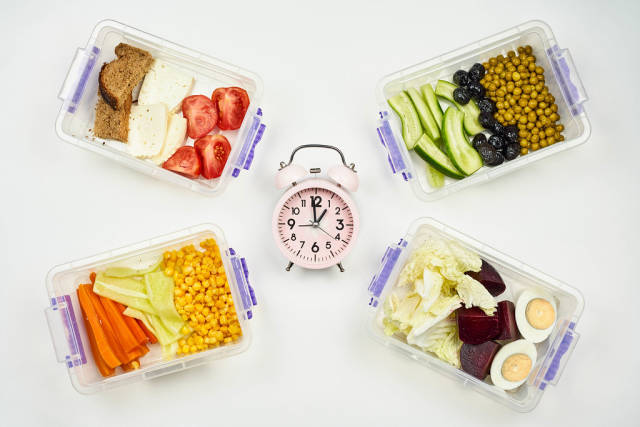 Its lunchtime. Alarm clock and food in lunchboxes