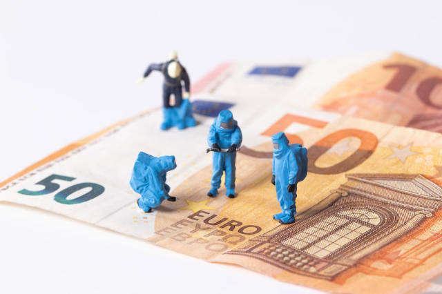 Workes in blue protective suits on Euro banknotes