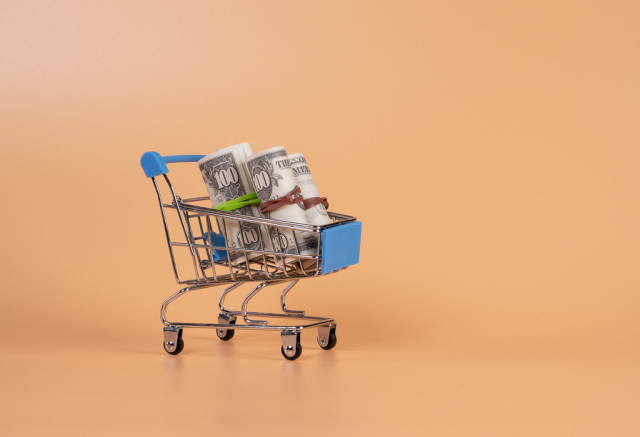 Rolls of dollar banknotes in shopping cart