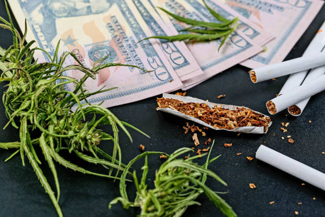Cannabis herb with money and cigarettes on black