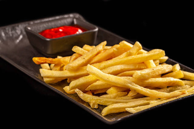 Fresh french fries and tomato sauce on a black background, close-up