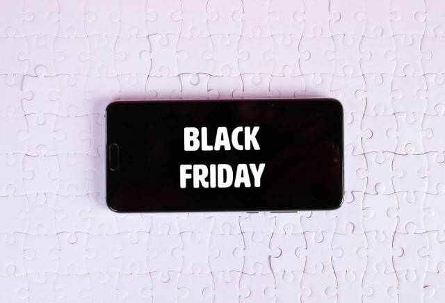 Smartphone on a white jigsaw puzzle with Black Friday text