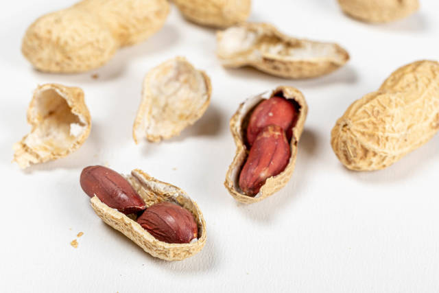 Raw peanuts in a whole shell and peanuts in a broken shell on a white background