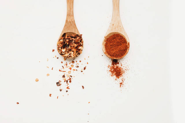 Top view of two wooden spoons with chili flakes and paprika powder on white background