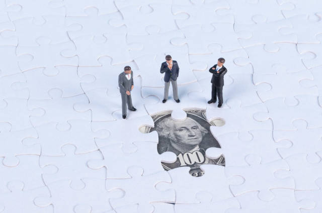 Group of businessman with missing jigsaw puzzle pieces on money dollar background