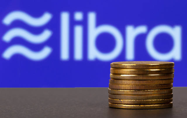 Golden coins stacked in front of Libra cryptocurrency logo