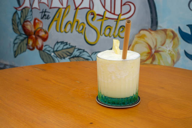 Refreshing Virgin Pina Colada in a Cocktail Glass with Bamboo Straw and Slice of Pinapple on a Wooden Table with Hawaii the Aloha State Drawing in the Background