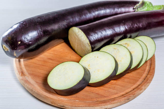 Whole and sliced ripe eggplant on the kitchen Board