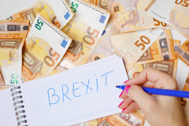 Woman hand writing Brexit, 50 Euro banknotes background