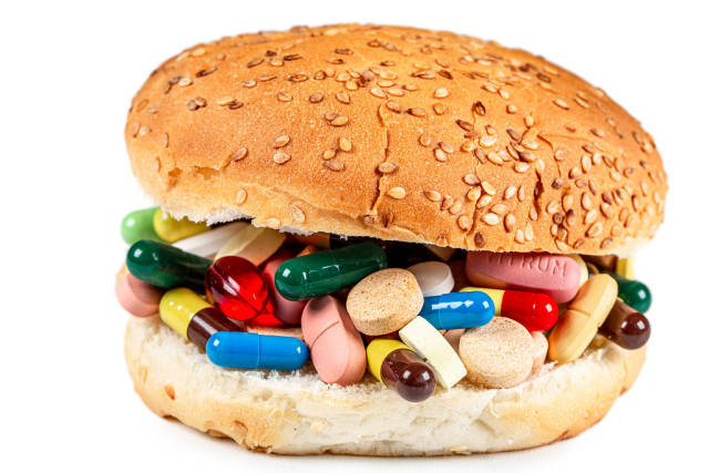 Close-up burger with medicines and pills inside on white