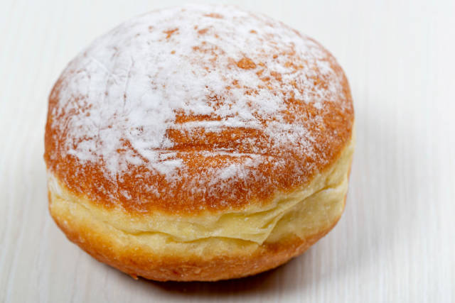 Traditional doughnut on white wooden background with powdered sugar