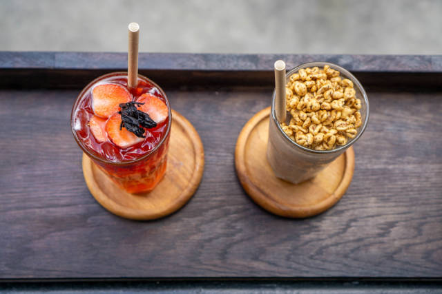 Top View Photo of  Milkshake with Puffed Rice Cerals and Strawberry Iced Tea in Cocktail Glasses with Paper Straws on a Wooden Balcony Table at a Cafe