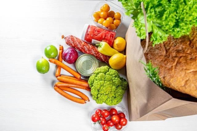 Eine Papiertasche voller Lebensmittel, wie Obst, Gemüse, Würstchen und Konserven