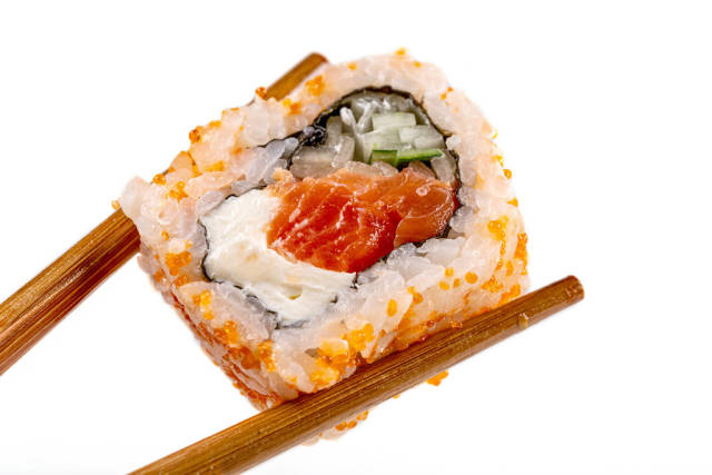 California roll with salmon and chopsticks, close-up