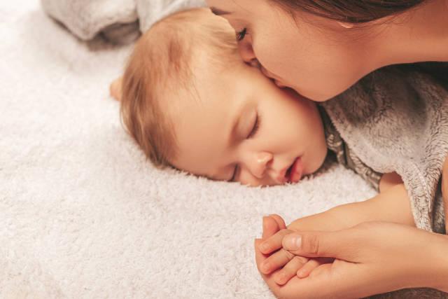 Mom kisses her little sleeping child on the cheek