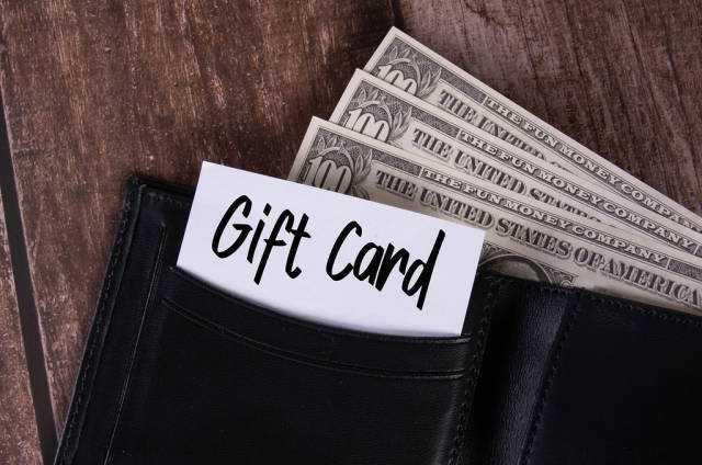 Black leather wallet with Dollar banknotes and note with Gift Card text