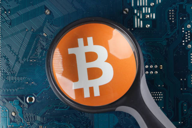 Bitcoin ogo over electronic circuit board background