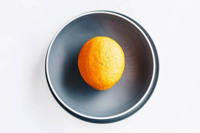 Draufsicht einer Orange auf grauem Teller