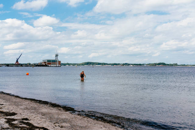 Senior woman going into the waters of Baltic Sea with crutch