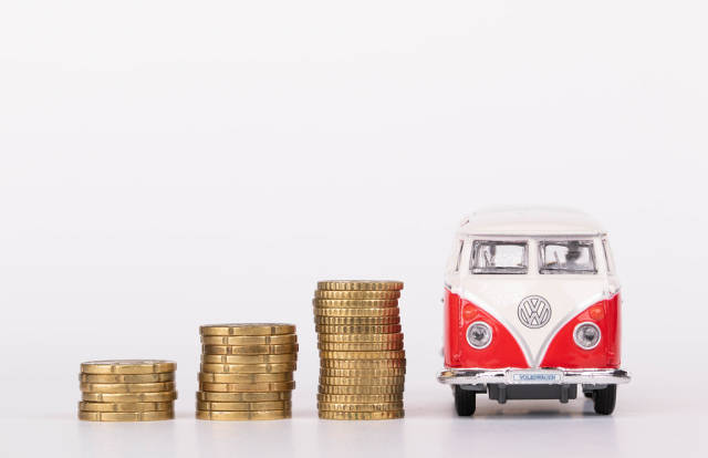Stacks of coins and retro car on white background