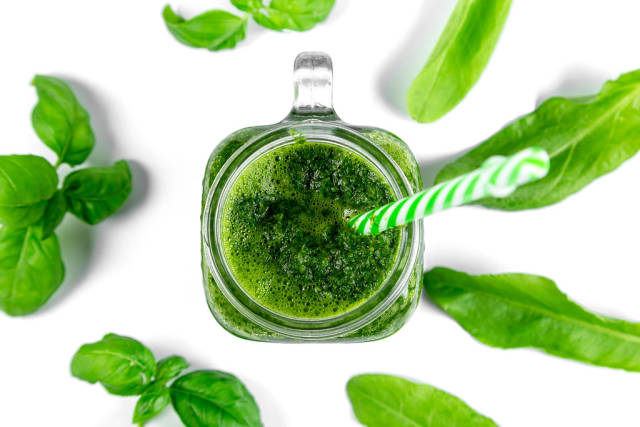 Top view, green smoothie with fresh leaves on a white background. Healthy food concept