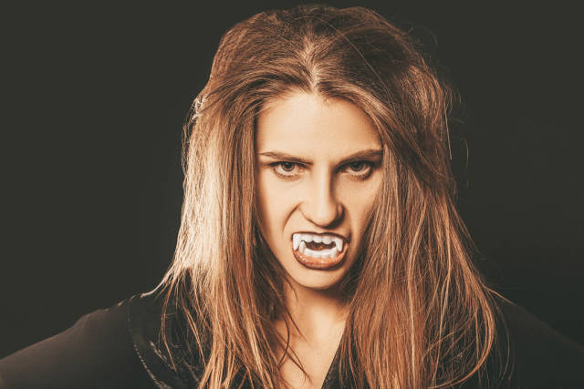 Halloween portrait of vampire woman with sharp fangs