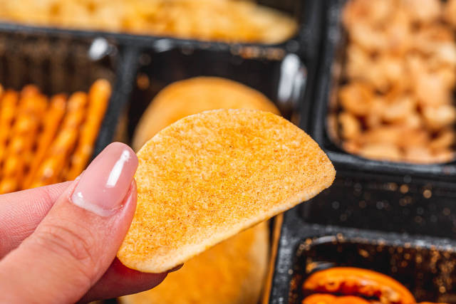 Chips in a womans hand close - up on the background of beer snacks