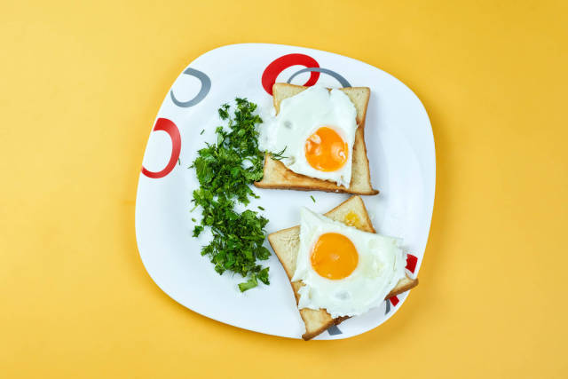 Fried egg with toast bread and parsley on white plate