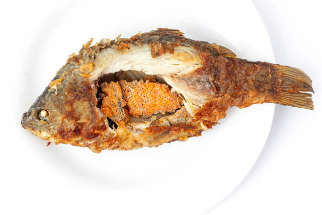 Top view of fried crucian carp with caviar on a white plate