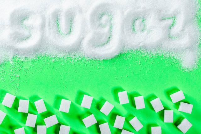 Text SUGAR mit Finger in Kristallzucker geschrieben und mit Würfelzucker auf grünem Hintergrund