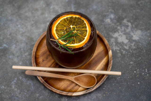 Trendgetränk Cold Brew Kaffee auf einem Holzuntersetzer mit Holzlöffel und Papierstrohhalm