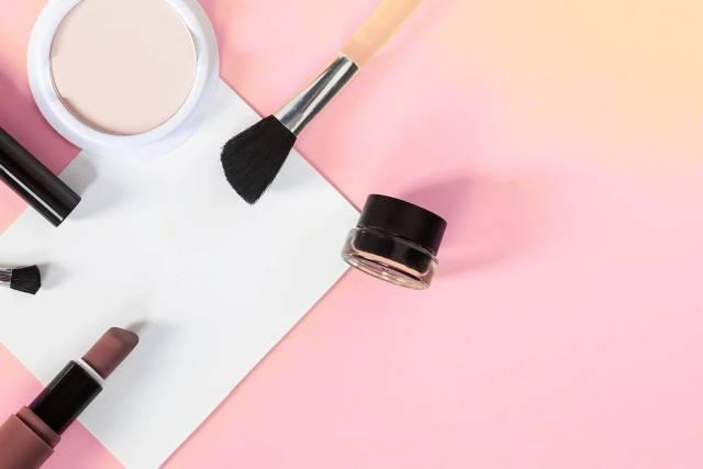 Kosmetik-Accessoires für Frauen-Make-Up, mit weißem Blatt auf rosa Hintergrund