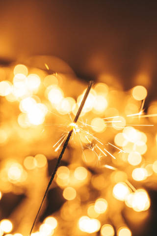 Bright burning sparkler on a blurred background of a glowing garland