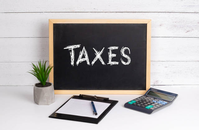 Blackboard with Taxes text