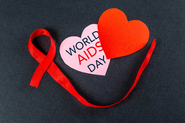 Aids day. Two hearts with red ribbon on a black background